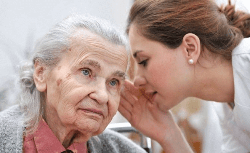 Aide soignante qui communique avec sa patiente atteinte de démence
